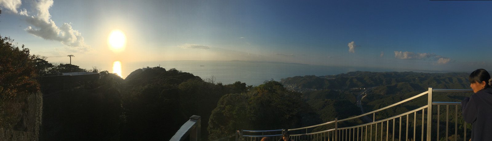 パノラマ写真。東京湾と三浦半島が見える、夕日が海に反射している。