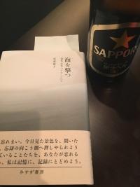 テーブルに置かれた書籍とその脇のビール瓶