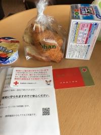 テーブルに並べられた献血カード、アイスクリーム、パン、洗剤
