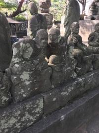陽光の下で隣に話しかける羅漢の石像