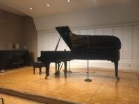 ステージ中央に置かれた黒いグランドピアノ